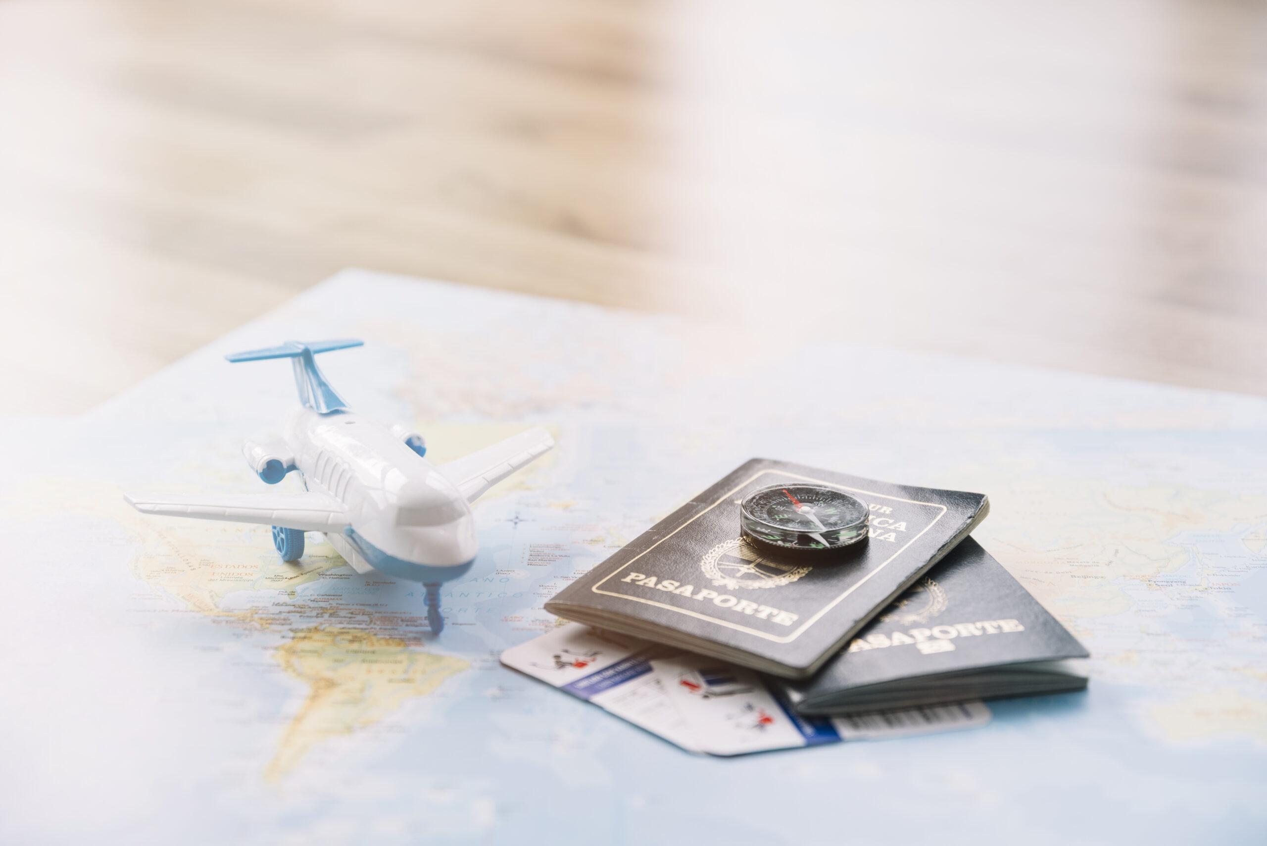 Passaportes ao lado de miniatura de avião e de mapa-mundi: saiba quais países aceitam cidadania por casamento