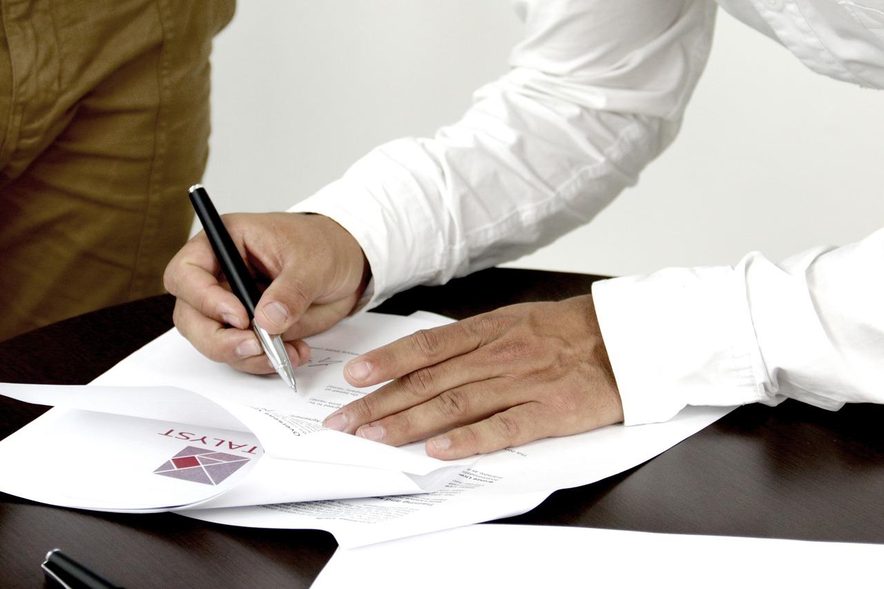Homem assina documento: veja como fazer a fazer a declaração de saída definitiva do país